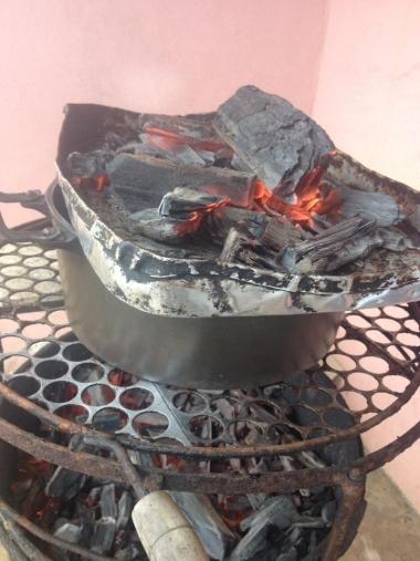 Caçarola na churrasqueira tampada com assadeira cheia de brasa