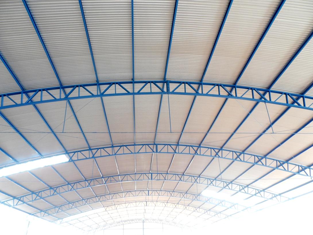 Galpão em estrutura metálica no modelo em arco com cobertura e pilar de alvenaria.